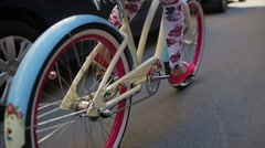 Back side of girl cycling in summer day wheel of a bicycle focus in. Slow motion - stock footage