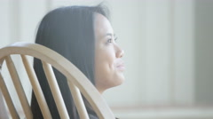 Asian woman in rocking chair looking down Stock Footage