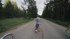 Man on bicycle set fire and start cycling with group of people in summer evening Stock Footage