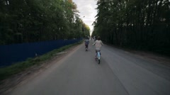 Back side of cycling group of people in a park in summer evening. Slow motion - stock footage