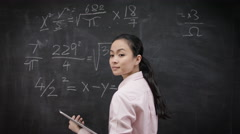 4K Teacher writing math formulas on blackboard & talking to her class Stock Footage