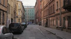 View of city street with signs and cars in summer evening. Camera moves forward Stock Footage
