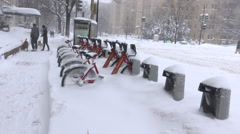 Bike Share bikes in snow storm, tow truck passes Stock Footage