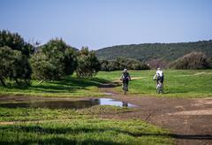 Couple of cyclist across a meadow - stock photo