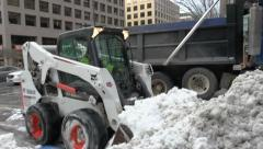 Close on snow exchanged, front loaders clearing street - stock footage