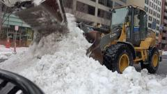Plow dumps snow into another, clearing downtown street - stock footage