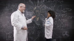 4K Little boy & mature man in white coats high five in front of blackboard - stock footage