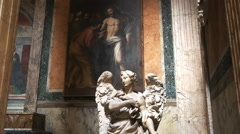 Tilt up shot of a statue of angel and a painting in the pantheon Stock Footage