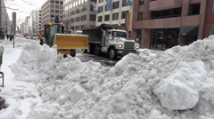 Front loader scoops snow, clearing downtown street Stock Footage