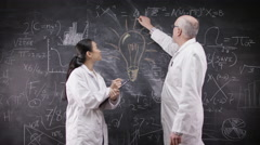 4K Man in white coat writing on blackboard & his younger assistant takes notes Stock Footage