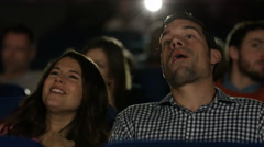 4K Couple watching film in busy movie theatre Stock Footage