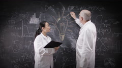 4K Scientists in white coats writing math formulas on blackboard & giving a high - stock footage
