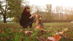 Stylish young lady teases her dog with a treat and sends him to bring it Stock Footage