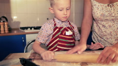 Mother and son rolling the dough for cake using rolling pin Stock Footage