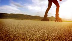 A person in roller-skates goes by the running track Stock Footage