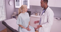 Black doctor talking with woman patient Stock Footage