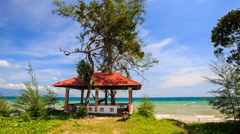 Red Roof Pavilion with Hammock on Beach against Azure Sea - stock footage
