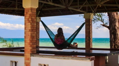 Camera Moves to Girl in Hammock in Red Roof Pavilion on Beach Stock Footage