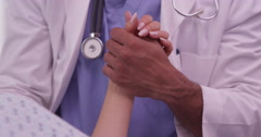 Closeup of African doctor holding patient's hand Stock Footage