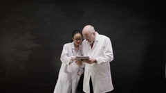 4K Portrait of man & woman in white coats, with a tablet computer - stock footage