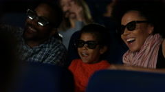 4K Young family watching a film with 3D glasses in crowded movie theatre - stock footage