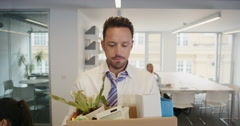 Businessman getting fired carrying box of personal belongings being made Stock Footage