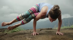 Fit yoga girl doing power pose on top of hill Stock Footage