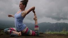 Beautiful yoga woman practising yoga on top of mountain Stock Footage