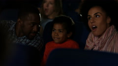 4K Young family watching a film in crowded movie theatre - stock footage
