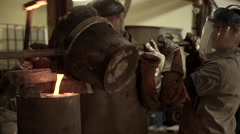 Steel worker in protective clothing raking furnace in an industrial foundry Stock Footage