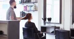 Pretty young woman leaning back and having her hair washed at the salon Stock Footage