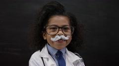 4K Portrait of happy cute little scientist standing in front of blank blackboard Stock Footage
