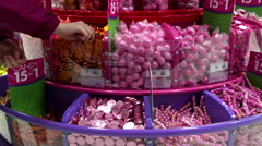 Woman selecting coin chocolate inside Party store Stock Footage