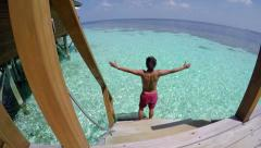 Young man walking from a room into the sea, sea resort in Maldives. - stock footage