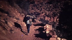 1972: Boy walking up dusty rocky mountain trail with backpack. - stock footage