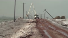 Power line workers in ice storm on muddy road - stock footage