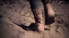 1972: Worn boots closeup walking up dusty dry desert hiking trail. - stock footage