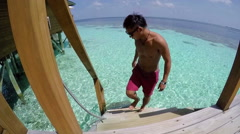Young man walking from a room into the sea, sea resort in Maldives. Stock Footage