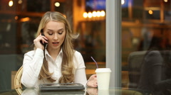 Businesswoman swears on the phone sitting in a cafe. It uses a Tablet PC Stock Footage