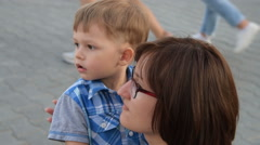 Mother and child watching something in the street Stock Footage