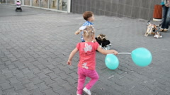 Boy and girl with balloons playing in the street Stock Footage
