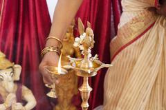 Woman lighting up the metal oil lamp - stock photo