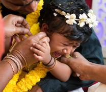 Traditional Indian family ear piercing ceremony - stock photo