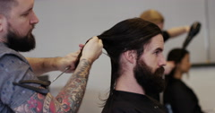 Happy cheerful hairdresser chatting to his client and giving a hair cut. - stock footage