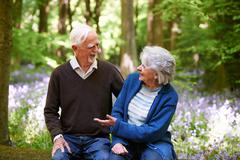 Senior Couple Sitting On Log In Bluebell Wood - stock photo