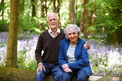 Stock Photo of Senior Couple Sitting On Log In Bluebell Woods