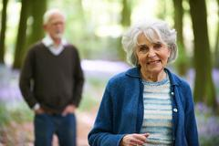 Senior Couple Walking Through Bluebell Woods - stock photo
