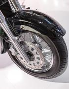 The front tire of a parked custom motorcycle - stock photo