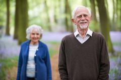 Senior Couple Walking Through Bluebells Woods - stock photo