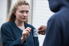 Teenage Girl Buying Drugs On The Street - stock photo